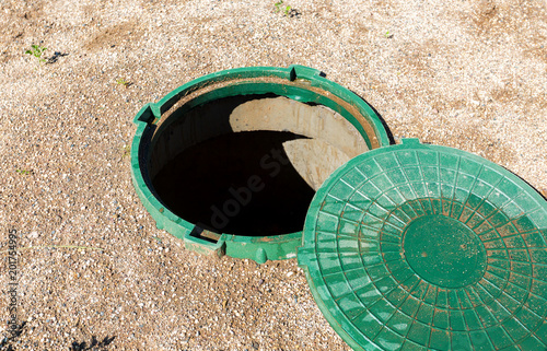 Valokuvatapetti Opened unsecured sewer manhole of rural septic tank with green plastic cover