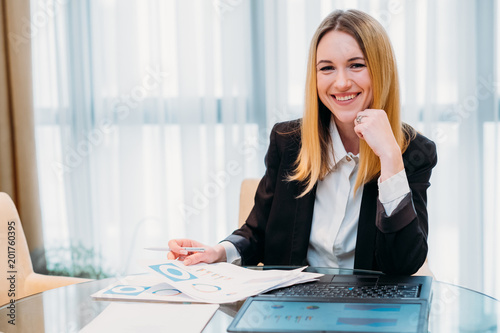 Fototapeta business lady at work. company manager. woman smiling into camera sitting at her workplace. professional corporate executive obraz