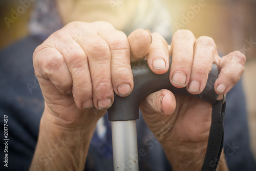 Fotografie, Obraz  close-up of old dirty wrinkled woman hands holding walking stick