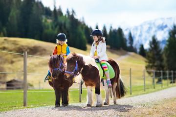 Dzieci jeżdżące na kucyku. Dziecko na koniu w Alpach góry
