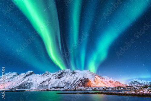 Obraz Aurora borealis. Lofoten islands, Norway. Aurora. Green northern lights. Starry sky with polar lights. Night winter landscape with aurora, sea with sky reflection and snowy mountains.Nature background - fototapety do salonu