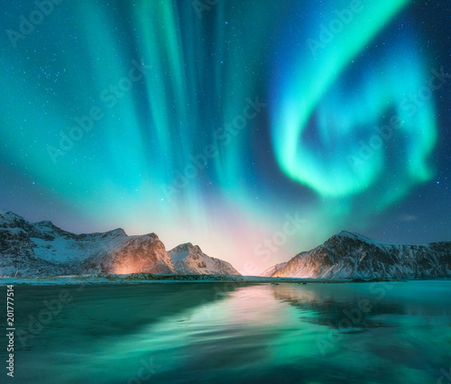 Fotobehang Noorderlicht Aurora borealis in Lofoten islands, Norway. Aurora. Green northern lights. Starry sky with polar lights. Night winter landscape with aurora, sea with sky reflection, stones, beach and snowy mountains