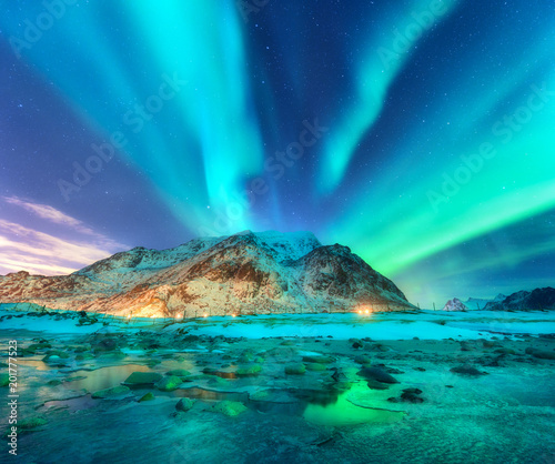 Foto op Plexiglas Blauwe jeans Aurora. Northern lights in Lofoten islands, Norway. Starry sky with polar lights. Night winter landscape with aurora, sea with sky reflection, stones, sandy beach and mountains. Green aurora borealis