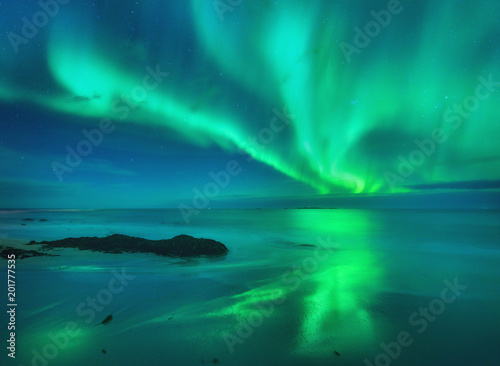 Poster Aurore polaire Aurora on the sea. Northern lights in Lofoten islands, Norway. Starry sky with polar lights. Night landscape with aurora, sea with blurred water and sky reflection, stones, sandy beach.Aurora borealis