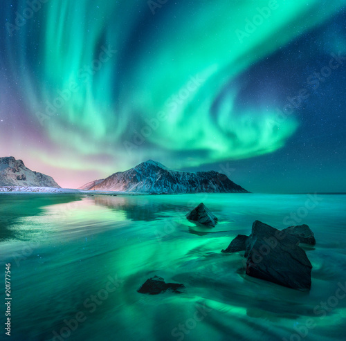 Photo Stands Green blue Aurora. Northern lights in Lofoten islands, Norway. Sky with polar lights, stars. Night winter landscape with aurora, sea with sky reflection, stones, sandy beach and mountains. Green aurora borealis
