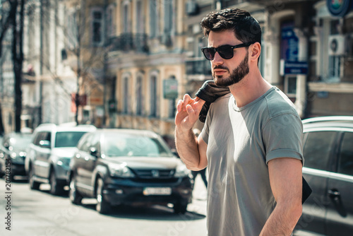 Fotografie, Obraz  A bearded man wearing sunglasses walks in a hot summer forest with a jacket on his shoulder