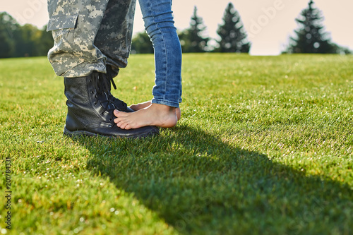 Papiers peints Jardin Close up feet of soldier and daughter. Leather military boots and naked feet on the meadow.