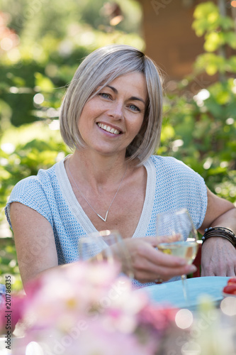 Fotografia  Portrait of a beautiful woman in her forties, sits at a table