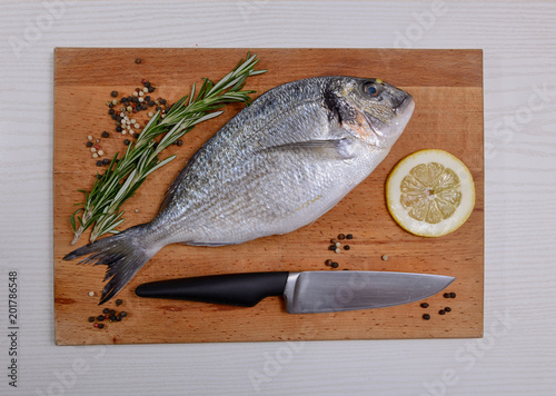 In de dag Vis Fresh dorado fish with rosemary lemon, pepper and knife on wooden cutting board