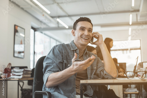 Papiers peints Retro Portrait of beaming male speaking by phone while gesticulating hand. He having job in office. Glad employer telling during labor concept
