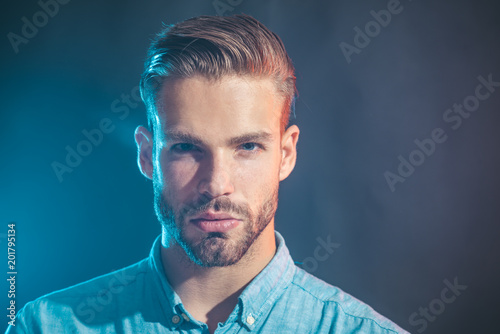 Emotions, feelings, facial expressions concept - serious fashionable bearded man. Sexy handsome unshaven man in denim shirt. Sexy male model thinking on something. Attractive man in casual clothing.