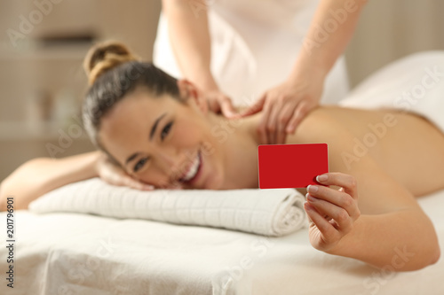 Woman receiving a massage showing credit card