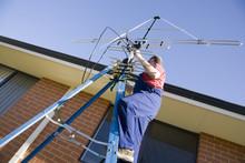 A Man Climbing A Ladder With A Television Aerial. A Repair Or Install.
