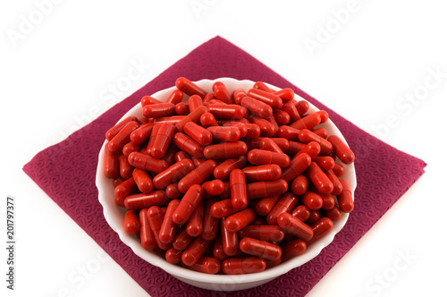 White porcelain cup filled with red capsules with medicine
