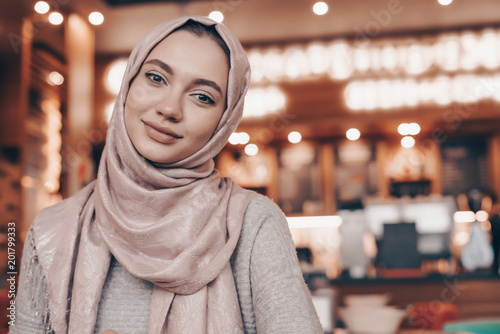 Photo beautiful oriental girl with headscarf on head wearing hijab, sitting in cozy ca