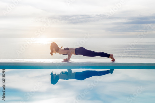 Fotobehang Ontspanning Asian young woman practice yoga Plank or Phalakasana Pose on the beach with beautiful sea,Feeling so comfortable and relax in holiday