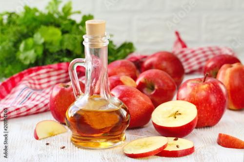 Apple vinegar. Bottle of apple vinegar on wooden background.