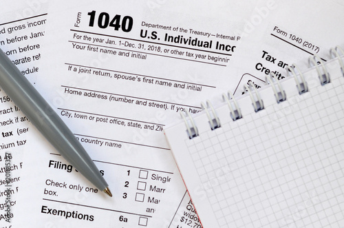 Fotografía  The pen and notebook is lies on the tax form 1040 U