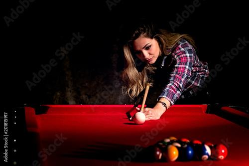 Foto Young woman playing billiards in the dark billiard club