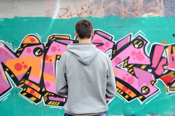 A young graffiti artist in a gray hoodie looks at the wall with his graffiti in pink and green colors on a wall in rainy weather. Street art concept