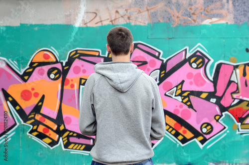 plakat A young graffiti artist in a gray hoodie looks at the wall with his graffiti in pink and green colors on a wall in rainy weather. Street art concept