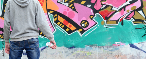A young graffiti artist in a gray hoodie looks at the wall with his graffiti in pink and green colors on a wall in rainy weather. Street art concept - 201824162