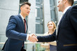 Content handsome young new business employee shaking hand of colleague while getting acquainted with team in office