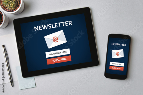 Subscribe newsletter concept on tablet and smartphone screen over gray table. All screen content is designed by me. Flat lay
