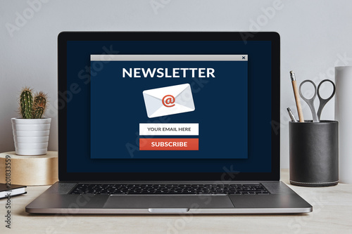 Subscribe newsletter concept on laptop screen on modern desk. All screen content is designed by me. Front view.