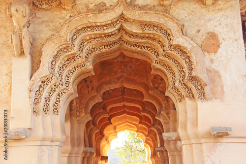Wall Murals Place of worship Lotus Mahal Temple in Hampi, Karnataka, India.Beautiful carved stone arch and sunset. A popular tourist route from the GOA state. Beautiful hindu temple