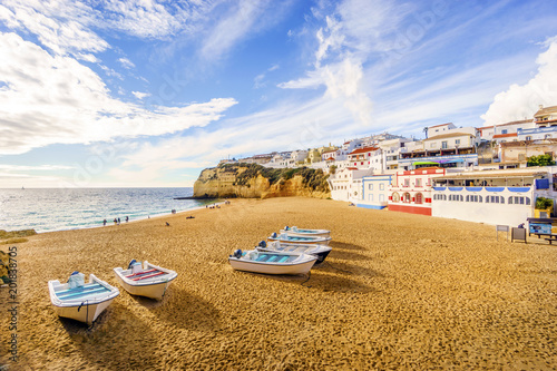 Fototapeta Sandy beach with colorful boats and cliffs and white architecture in Carvoeiro, Algarve, Portugal obraz na płótnie