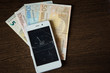 smartphone with broken screen on a background of Euro bills. Saving
