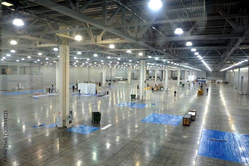 Foto op Plexiglas Industrial geb. Large empty warehouse interior in an industrial building with high vertical columns with and high ceiling and artificial lighting horizontal view