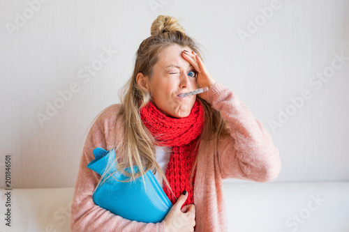 Fotografia Funny picture of sick woman measuring temperature with thermometer in her mouth