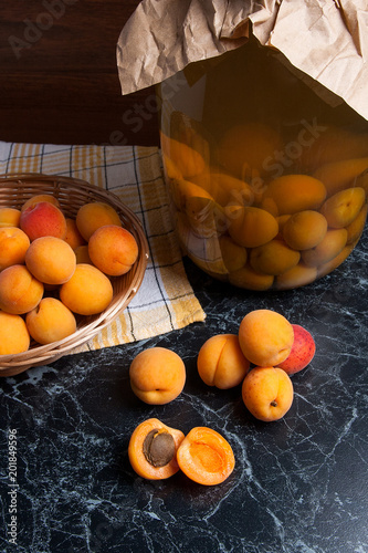 Fresh organic harvested apricots in basket and big glass jar with canned apricot compote on dark marble..