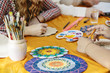 Women's hands, brushes and paints close-up draw on artistic training to create the mandala of life