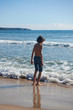 Teen boy walking in shallow water