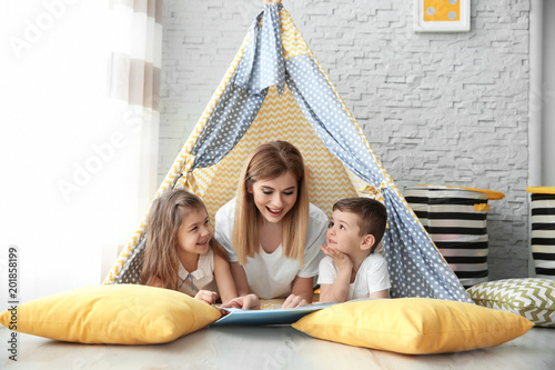 Photo Nanny and little children reading book in tent at home