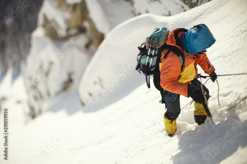 Poster Alpinisme Mountaineer clinging to a rope on a steep snow-covered mountain slope. Tilt-shift effect.