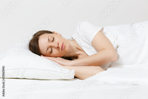 Fototapeta Calm young brunette woman lying in bed with white sheet, pillow, blanket on white background. Sleeping beauty female spending time in room. Rest, relax, good mood concept. Copy space for advertisement obraz na płótnie