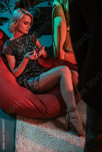 Glamorous woman sitting in beanbag and holding glass with cocktail Wallpaper Mural