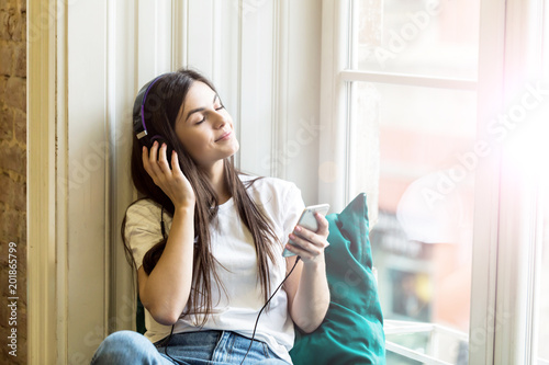 Long hair sexy girl wears headphones and white t-shirt listen to music sitting on wide windowsill - 201865799