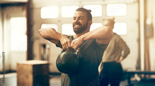 Poster Fitness Fit young man smiling while lifting dumbbells in a gym
