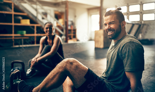 Fotografía  Smiling people relaxing on a gym floor after working out