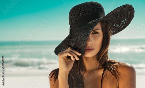 Obraz Fashion woman with straw hat at beach - fototapety do salonu