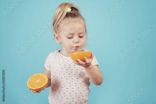Valokuvatapetti bebé comiendo una naranja sobre fondo azul