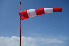 Red & White Airfield Windsock Against A Blue Sky