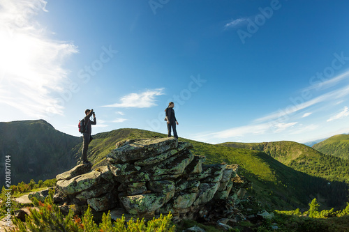Photo  young couple photographed on a rock in the mountains view