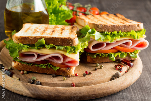 Keuken foto achterwand Snack Close-up photo of a club sandwich. Sandwich with meet, prosciutto, salami, salad, vegetables, lettuce, tomato, onion and mustard on a fresh sliced rye bread on wooden background. Olives background.