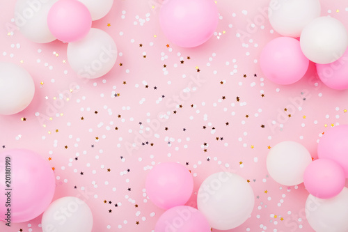 Pastel pink table with frame from balloons and confetti for birthday top view. Flat lay composition.